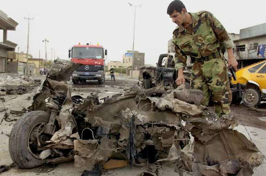 A soldier inspects the wreckage of a vehicle used in a suicide car bomb attack, which targeted a police patrol in Kirkuk, about 250 km (150 miles) north of Baghdad, October 15, 2006. Four car bombs exploded in apparently coordinated attacks in the restive northern Iraqi oil city of Kirkuk on Sunday, killing 10 people and emptying the streets as terrified residents stayed indoors. REUTERS/Slahaldeen Rasheed (IRAQ) Photo: SLAHALDEEN RASHEED