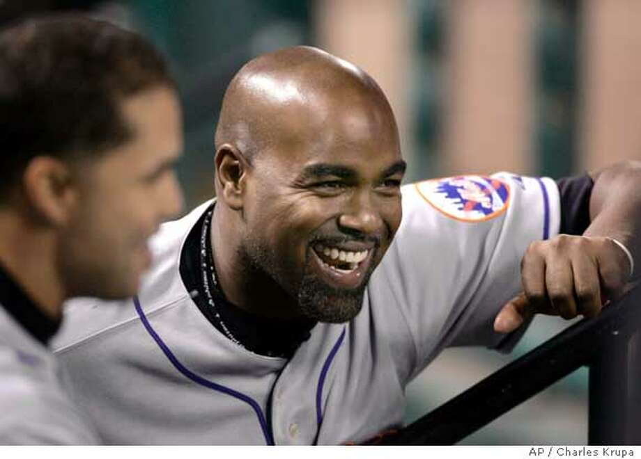 New York Mets' Carlos Delgado, right, and Carlos Beltran share a laugh in the dugout during the seventh inning during Game 4 of baseball's National League Championship Series against the St. Louis Cardinals, Sunday, Oct. 15, 2006, in St. Louis. (AP Photo/Charles Krupa) Photo: CHARLES KRUPA