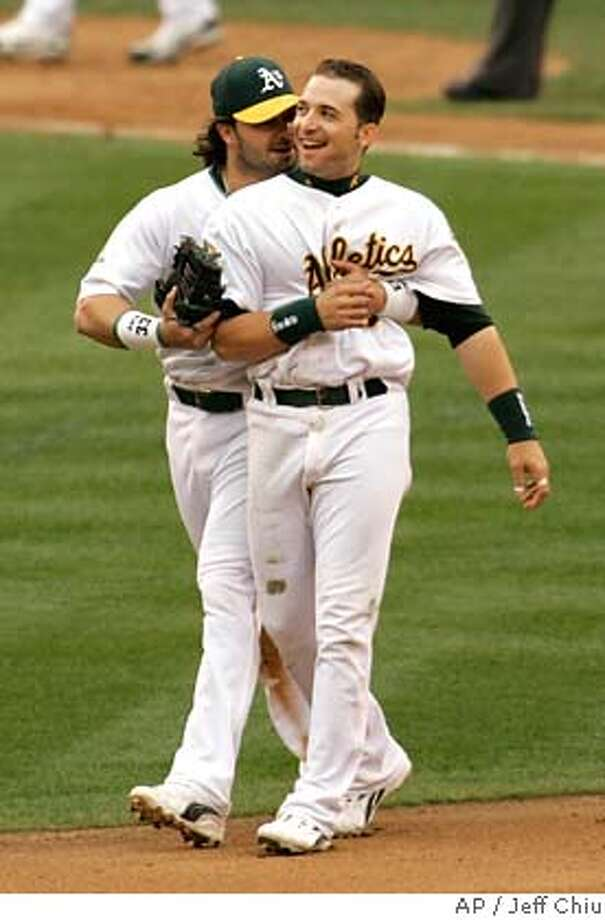 Oakland Athletics' Marco Scutaro, right, is hugged by teammate Nick Swisher at the end of the seventh inning of Game 3 of their American League Divisional Series baseball game against the Minnesota Twins, Friday, Oct. 6, 2006, at the Oakland Coliseum in Oakland, Calif. Scutaro doubled twice and tied an Oakland postseason record with four RBIs. The Athletics won, 8-3, to win the best of 5 game series, 3-0. (AP Photo/Jeff Chiu) Photo: JEFF CHIU