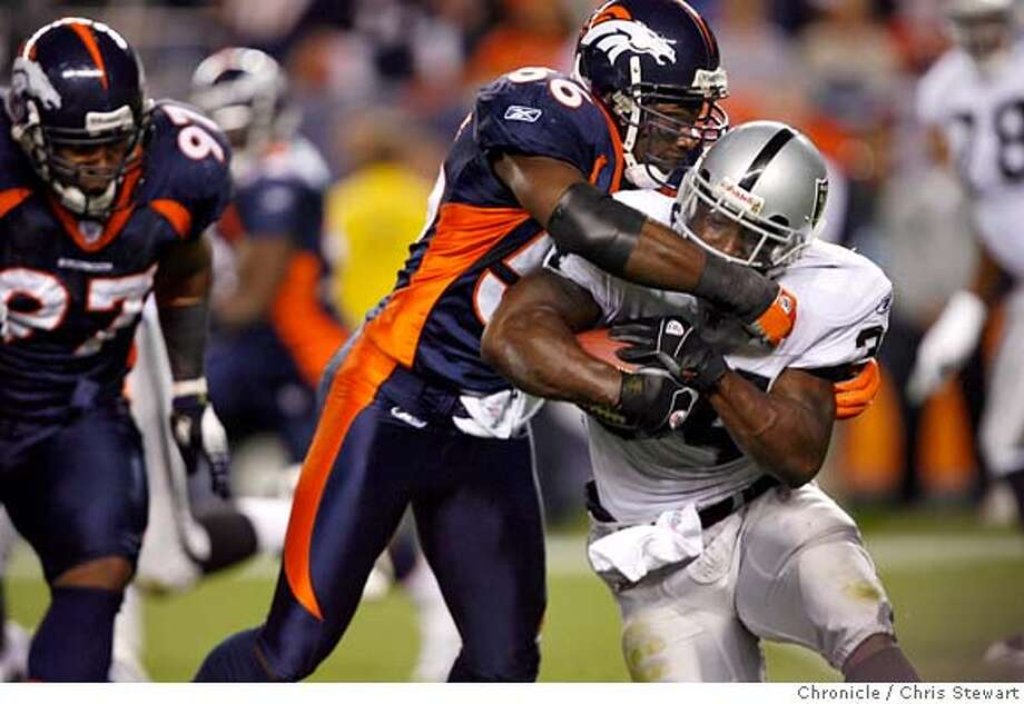 The Raiders LaMont Jordan is brought down short by the Broncos' Al Wilson in the second quarter, forcing them to punt. The 0-4 Oakland Raiders trail the 3-1 Denver Broncos 13-0 at half time, Sunday, October 15, 2006 at Invesco Field at Mile High in Denver, Colorado. Chris Stewart / The Chronicle Oakland Raiders, Denver Broncos Photo: Chris Stewart