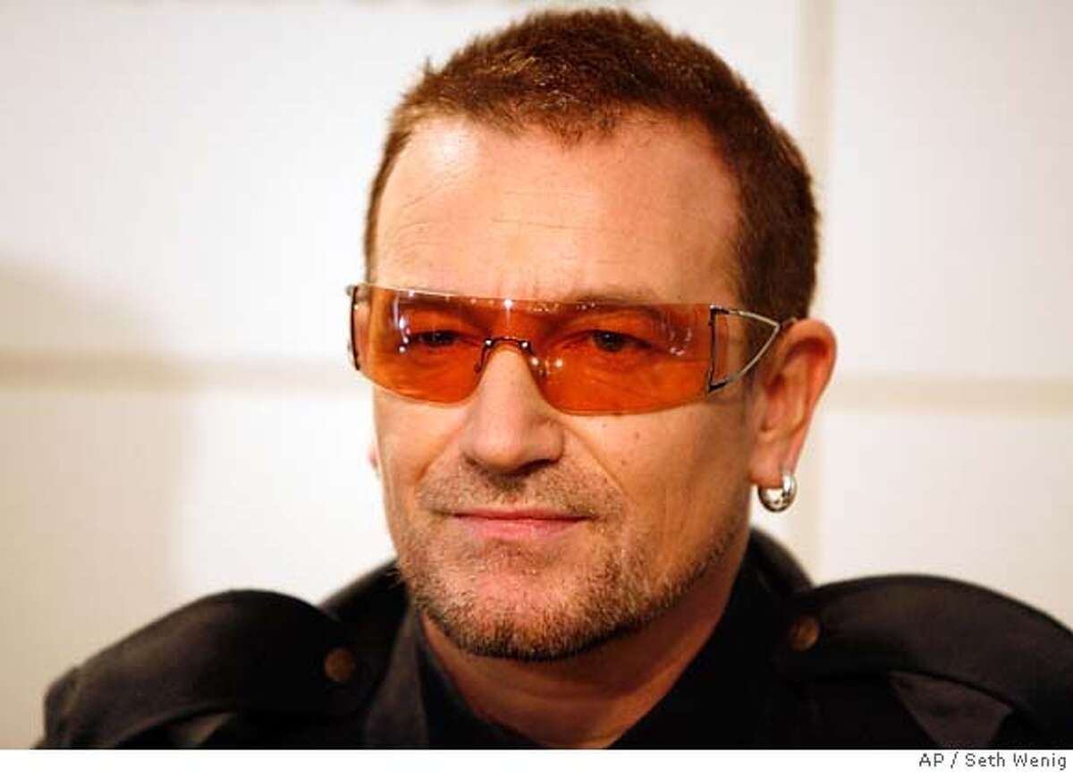 """Bono of the band U2 signs copies of the new book """"U2 by U2"""" Tuesday, Sept. 26, 2006 in New York. (AP Photo/Seth Wenig)"""