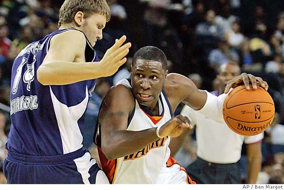 The Warriors' Mickael Pietrus of France drives past Turkey's Baris Hersek in Thursday's exhibition game in Oakland. Associated Press photo by Ben Margot