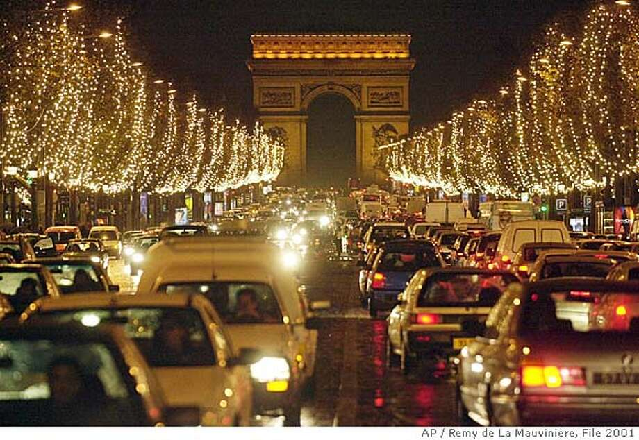 Christmas decorations illuminate the Champs Elysees Avenue in Paris, Thursday Nov. 29, 2001 as the Arc de Triomphe is seen in the background. The decorations are traditionally put up late November each year for Christmas. (AP Photo/Remy de La Mauviniere) ELECTRONIC IMAGE Photo: REMY DE LA MAUVINIERE