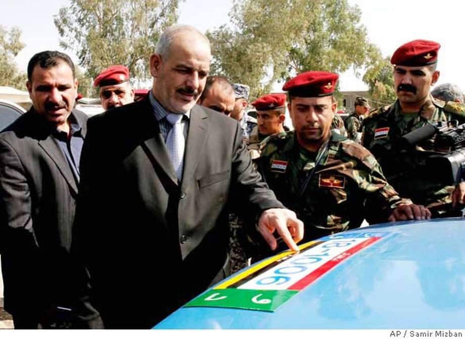 Iraq's interior minister, Jawad al-Bolani inspects a new design of licence plates to be issued to Iraqi police in Baghdad, Iraq, Monday, Oct. 9, 2006. Iraqi special police units were issued new uniforms and licence plates they claim would be difficult to forge. (AP Photo/Samir Mizban) Photo: SAMIR MIZBAN