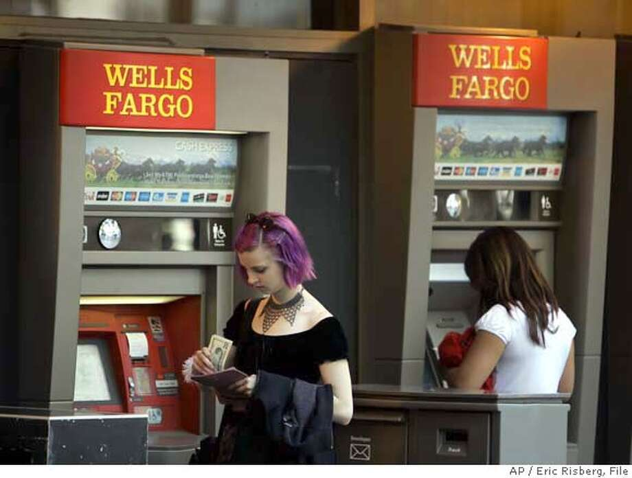 A woman puts away her money after visiting a Wells Fargo automated teller machine in San Francisco, Monday July 17, 2006. Wells Fargo & Co., the nation's fifth largest bank, reports record profits in the second quarter, but the results are a penny shy of Wall Street's expectations. (AP Photo/Eric Risberg)  Ran on: 07-19-2006  Wells Fargo ATMs are ubiquitous in San Francisco and a steady fee generator. Photo: ERIC RISBERG