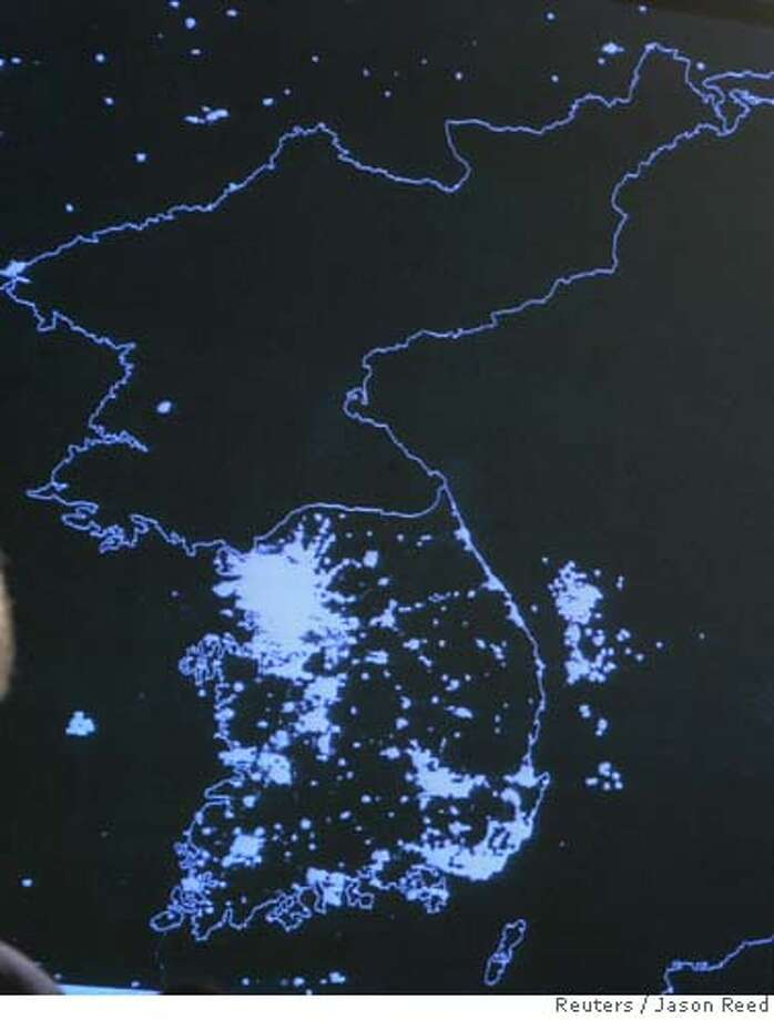 A satellite image from the U.S. Department of Defense of the Korean Peninsula at night, showing the lights of South Korea and the relative darkness of North Korea (TOP), is shown at a news briefing by U.S. Defense Secretary Donald Rumsfeld at the Pentagon in Washington, October 11, 2006. REUTERS/Jason Reed (UNITED STATES) 0 Photo: JASON REED