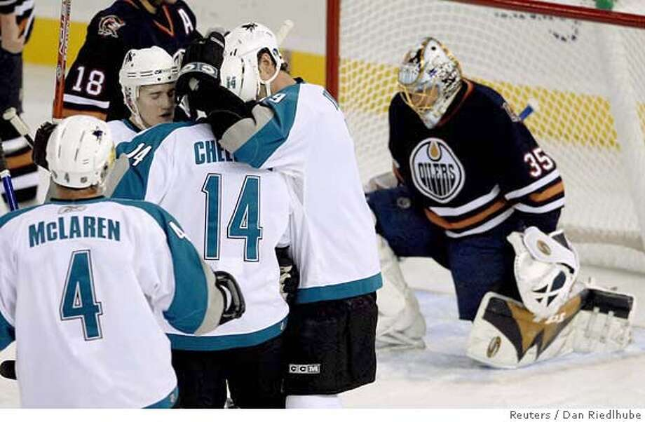 San Jose Shark (from L) Kyle McLaren, Matt Carle, Jonathan Cheechoo and Joe Thornton celebrate Cheechoo's goal against Edmonton Oilers goaltender Dwayne Roloson during first period NHL action in Edmonton October 12, 2006. REUTERS/Dan Riedlhuber (CANADA) 0 Photo: DAN RIEDLHUBER