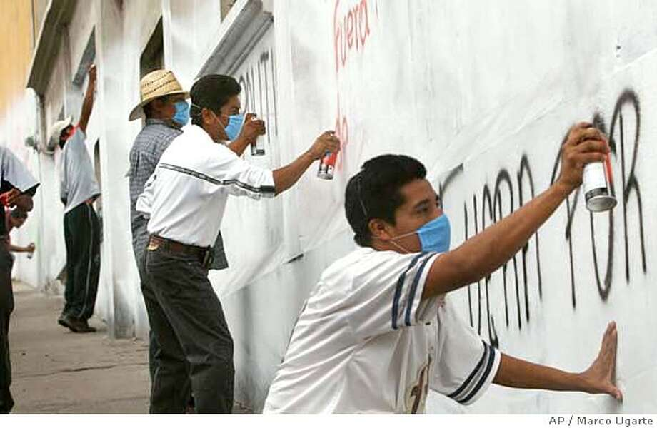 Members of the Popular Assembly of the People of Oaxaca, or APPO, write grafitti on the wall with their faces covered in Oaxaca Mexico, Wednesday, Oct. 11, 2006. They are demanding the resignation of Oaxaca State Gov. Ulises Ruiz. (AP Photo/Marco Ugarte) **EFE OUT** Photo: MARCO UGARTE