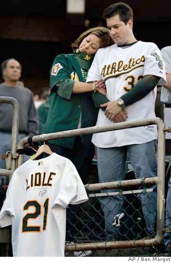 Carrie Olejnik, left and Francis Crimi of Los Altos, Calif., observe a moment of the silence in memory of New York Yankees Cory Lidle before the start of Game 2 of the American League Championship Series against the Oakland Athlethics in Oakland, Calif., Wednesday, Oct. 11, 2006. Lidle was killed when a small plane he was in slammed into a skyscraper in New York City on Wednesday. (AP Photo/Ben Margot) Photo: Ben Margot