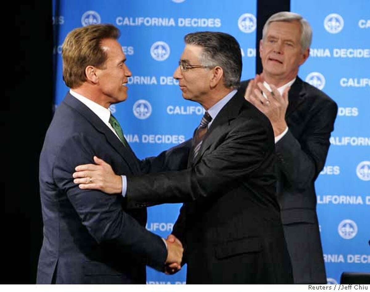 California Governor Arnold Schwarzenegger (L) shakes hands with opponent Phil Angelides after the Governors Debate 2006 as moderator Stan Stathern (R) of the California Broadcasters Association applauds at Sacramento State University in Sacramento, California October 7, 2006. REUTERS/Jeff Chiu/Pool (UNITED STATES) 0