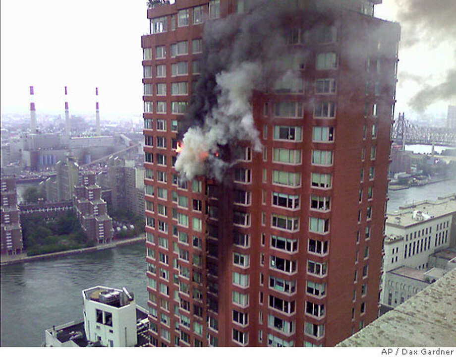 Flames and smoke are seen coming out of windows at the location where a small plane crashed into a 50-story residential apartment building near 71st Street and York Avenue in New York, Wednesday, October 11, 2006. New York Fire Department officials reported two deaths in the crash. (AP Photo/Dax Gardner) Photo: DAX GARDNER