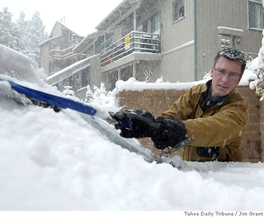 After finding a brush hidden beneath the golf clubs in the back of his SUV, Lake Tahoe resident Thom McAleer sweeps the windshield of about 4 inches of snow before heading into work in South Lake Tahoe, Calif., Tuesday, Oct. 11, 2006. (AP Photo/Tahoe Daily Tribune, Jim Grant) Photo: JIM GRANT