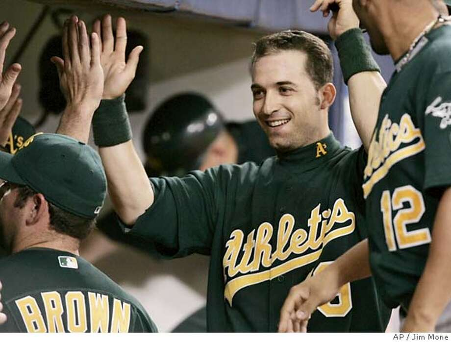 Oakland Athletics' Marco Scutaro is greeted in the dugout after scoring on a Jason Kendall single in the fifth inning in Game 2 of the American League Division Series baseball game Wednesday, Oct. 4, 2006 in Minneapolis. Scutaro drove in the first run with a double. (AP Photo/Jim Mone) Photo: JIM MONE