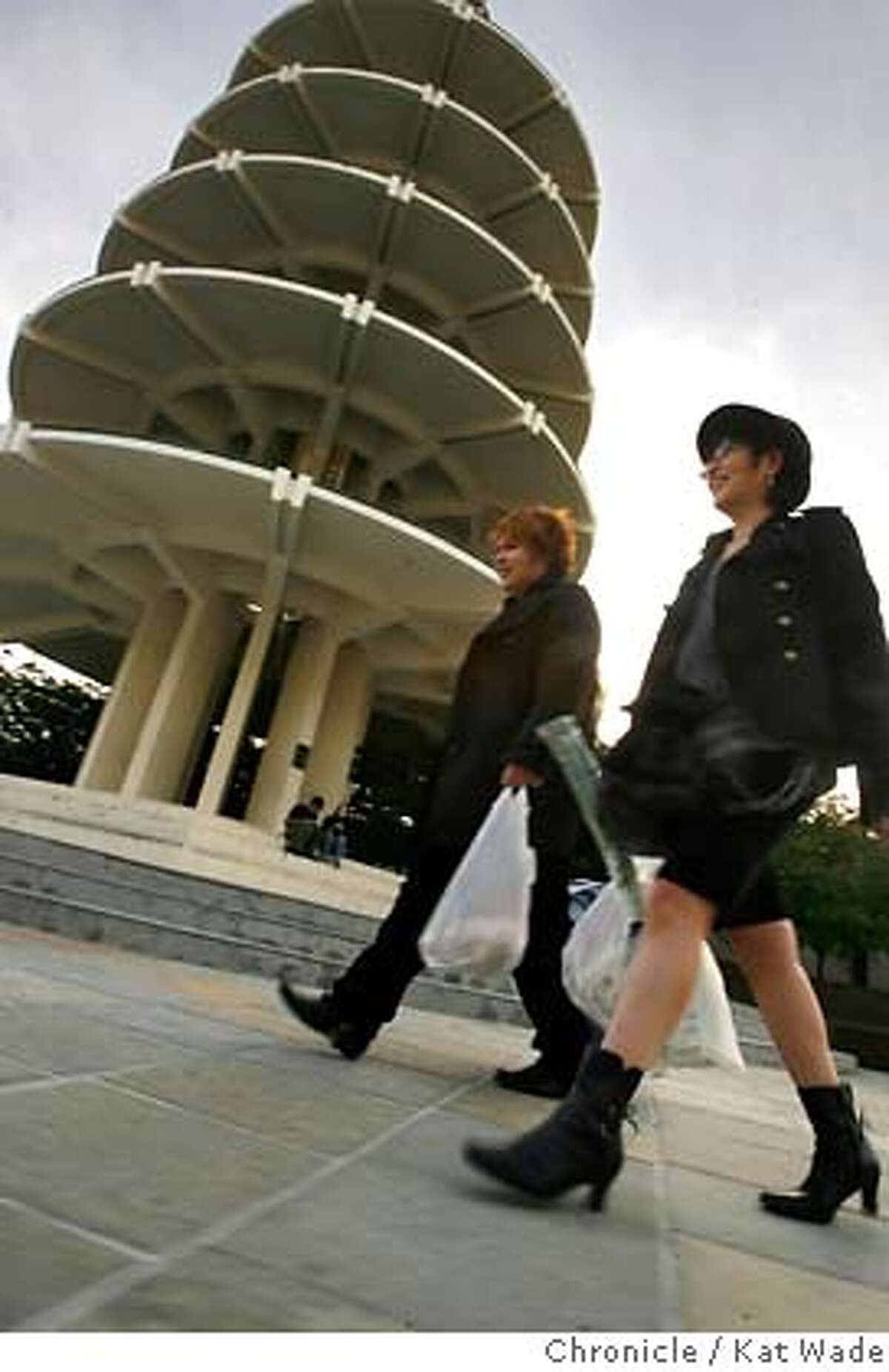 JTOWNPOP_0072_KW_.jpg (L TO R) Masaki Matsumoto from San Francisco and his mother, Chitose Matsumoto, who is visiting from Japan walk past the pagoda in Peace Plaza in Japantown Monday October 9, 2006. In the background New San Francisco residents Rudy Agtarap and Sachiko Ueyama sit beneath the pagoda. Kat Wade/The Chronicle Ran on: 10-10-2006 Masaki Matsumoto of San Francisco and his mother, Chitose Matsumoto, visiting from Japan, walk past the Peace Plaza pagoda.