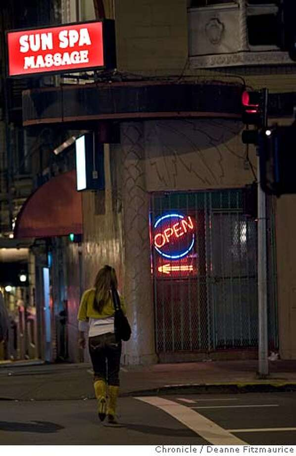 You-Mi Kim, a sex trafficking victim, walks through the Tenderloin past the Sun Spa where she used to work. She now lives in San Francisco and is out of the sex business. She is now a student. Photographed in San Francisco on 11/23/05.  (Deanne Fitzmaurice/ The Chronicle) Photo: Deanne Fitzmaurice