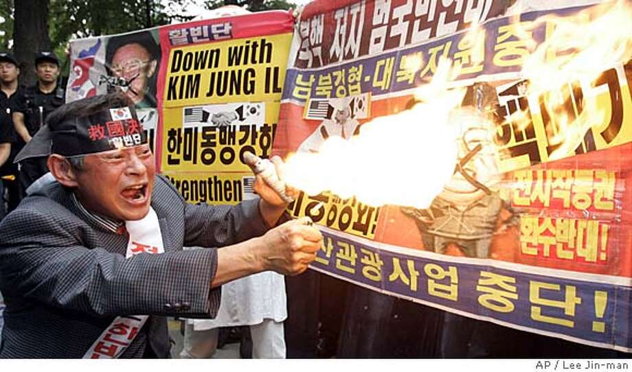 """A South Korean protester burns a banner bearing a picture of North Korean leader Kim Jong Il during an anti-North Korea rally in Seoul, Monday, Oct. 9, 2006. North Korea said Monday it performed its first-ever nuclear weapons test, claiming it set off a successful underground blast in a """"great leap forward"""" that defied international warnings against the communist regime. The Korean read """" Nuclear Abolition."""" (AP Photo/ Lee Jin-man) Photo: LEE JIN-MAN"""