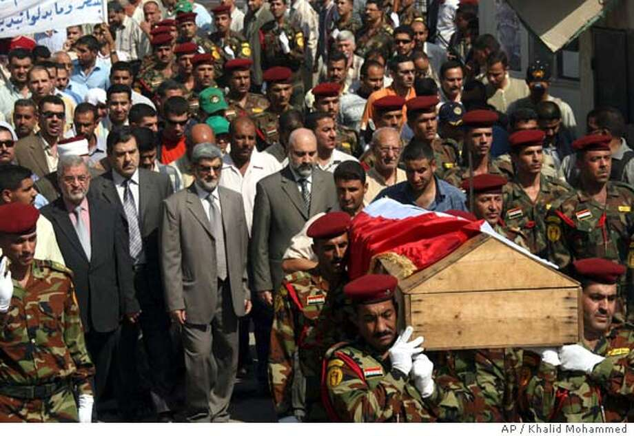 Iraqi soldiers carry coffin with remains of Gen. Amir al-Hashimi, the brother of Vice President Tariq al-Hashimi and an adviser to the Defense Ministry, during his funeral in Baghdad Monday Oct. 9, 2006. Al-Hashimi was killed by gunmen who entered his north Baghdad home wearing military uniforms Monday. (AP Photo/Khalid Mohammed ) Photo: KHALID MOHAMMED