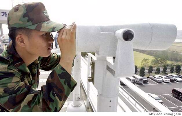 A South Korean Army soldier looks at the northern side through a pair of binoculars at the Imjingak Pavilion, near the demilitarized zone (DMZ) of Panmunjom, north of Seoul, South Korea, Sunday, Oct. 8, 2006. North Korea's threatened nuclear test moved to the top of the diplomatic agenda Sunday as Japanese Prime Minister Shinzo Abe flew to China to try to coordinate international pressure on Pyongyang to desist. (AP Photo/Ahn Young-joon) Photo: AHN YOUNG-JOON