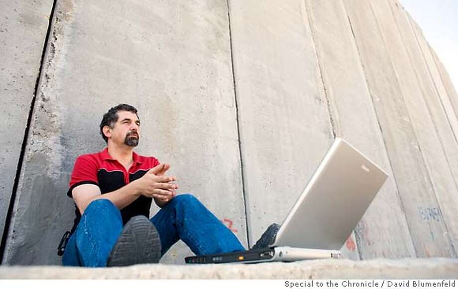"""Yair Amichai-Hamburger, who has developed conflict-resolution computer software, at the """"Separation Barrier"""" between Israel and the West Bank. Photo by David Blumenfeld, special to the Chronicle"""