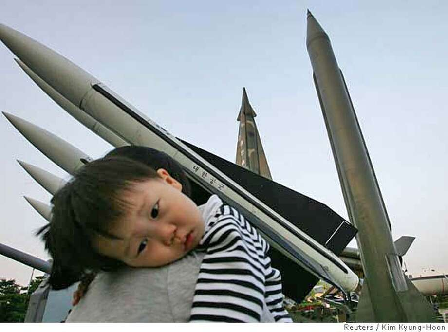 REFILE - CORRECTING POSITION OF MISSILES  A mother carries her son as they walk past models of North Korean Scud-B missile (R) and models of South Korean missiles at the war museum in Seoul October 7, 2006. South Korea fired warning shots on Saturday after North Korean soldiers briefly crossed into its side of their heavily defended border, adding to mounting tension after Pyongyang said this week it planned a nuclear test. REUTERS/Kim Kyung-Hoon (SOUTH KOREA) 0 Photo: KIM KYUNG-HOON