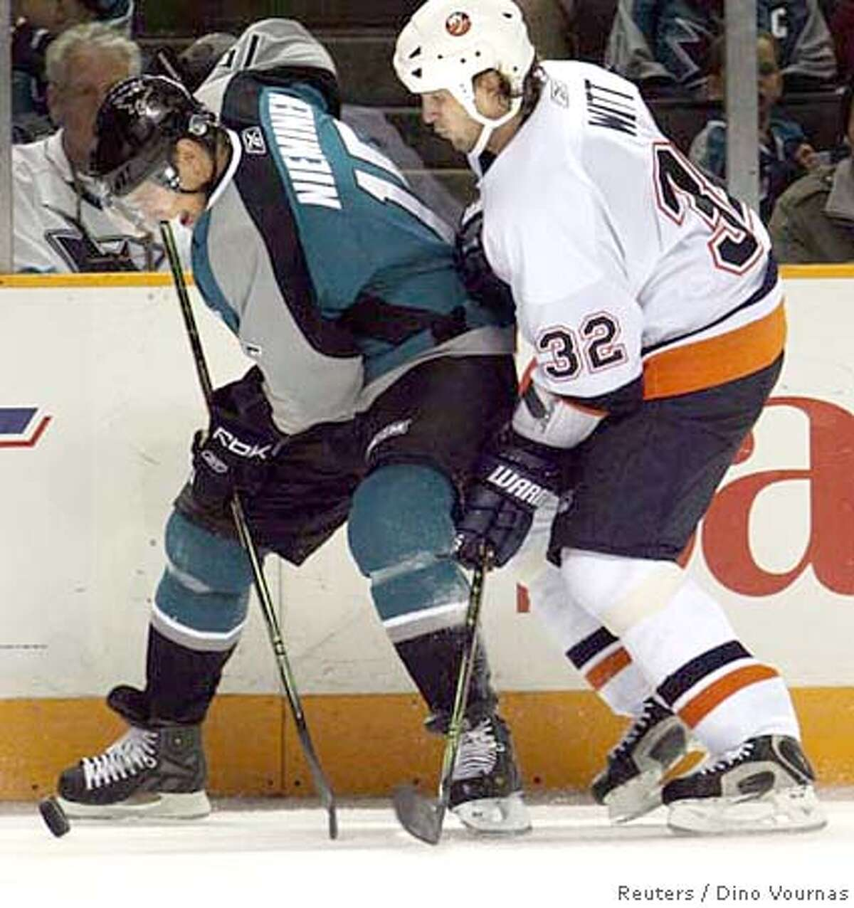 The San Jose Sharks' Ville Nieminen (L) of Finland battles Brendan Witt of the New York Islanders in the third period of an NHL hockey game in San Jose, California, October 7, 2006. REUTERS/Dino Vournas (UNITED STATES)