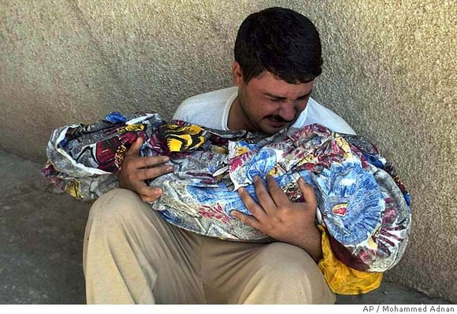 A Father weeps as he holds the body of his three-year old son Kerar Sadiq in Baquoba hospital yard, Iraq, Friday, Oct. 6, 2006. The boy was killed in a random shooting in front of a family home in Khan Bani Saad village outside Baquoba Thursday. (AP Photo/Mohammed Adnan) Photo: MOHAMMED ADNAN