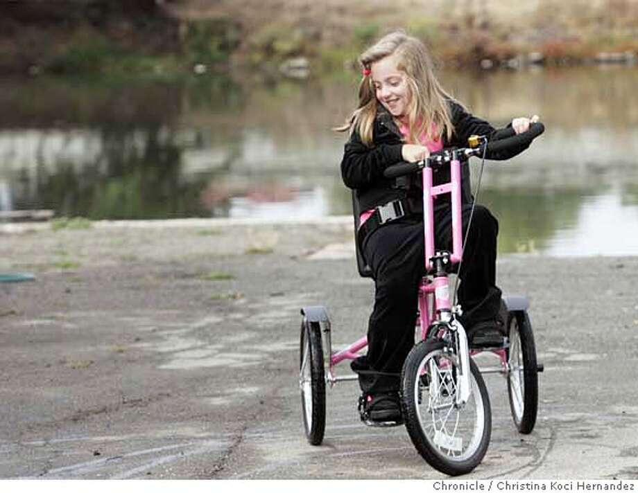 Marina Webb-Gordon, whose specially adapted tricycle was stolen from her Foster City apartment complex in May, rides her new trike Thursday thanks to a $2,000 donation from Wells Fargo. Marina, 8, has cerebral palsy and uses a tricycle to tag along with her friends, play at a nearby park and accompany her father on his bicycle. Wells Fargo's donation went to the Bay Area Outreach and Recreation Program in Berkeley, which built the new bike for Marina. Chronicle photo by Christina Koci Hernandez
