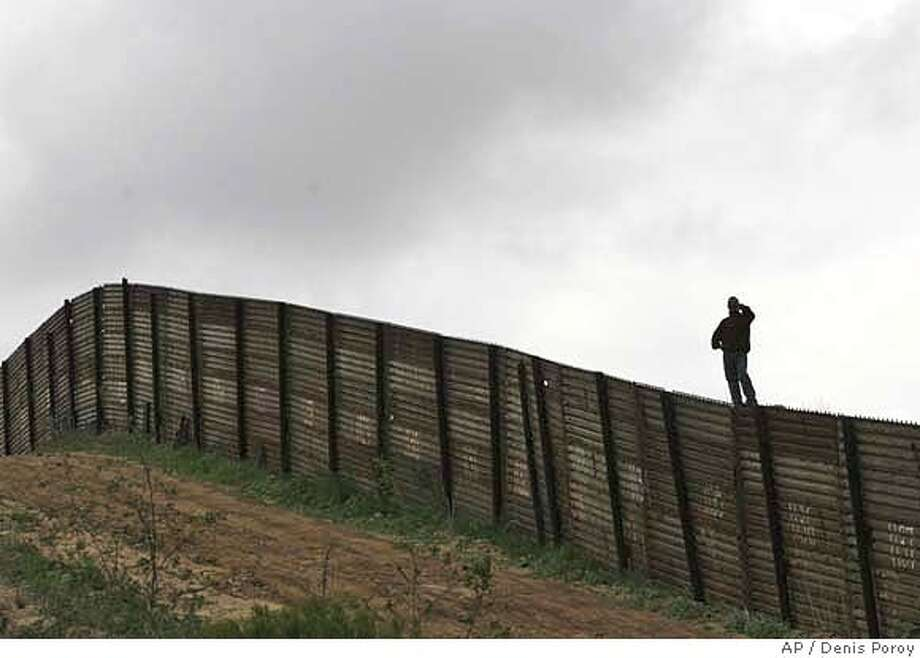 Hermin Ramos of Oaxaca, Mexico, peers over the U.S.-Mexico border fence west of the San Ysidro Port of Entry in San Diego. Associated Press photo by Denis Poroy