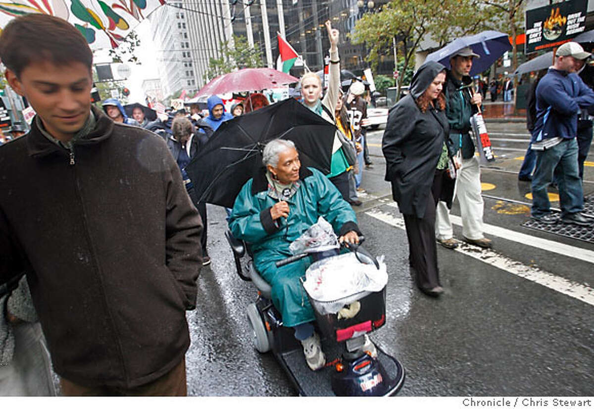 """Rain didn't damper the spirit of Toni Vincent, 71, as she joined hundreds of protesters marching up Market Street. """"I'm not carrying a sign because I hadn't planned to take part,"""" she explained. """"But I need to be here."""" Chronicle photo by Chris Stewart"""
