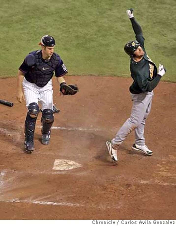 Mark Kotsay pumps his fist after scoring on an in-the-park homerun in the bottom of the seventh inning to give the A's a 4-2 lead, as Twins catcher, Joe Mauer looks on after failing to tag Kotsay out on the throw. The A's won 5-2. The Oakland Athletics played the Minnesota Twins in Game 2 of the American League Division Series at the Metrodome in Minneapolis, Mn., on Wednesday October 4, 2006, winning the game, 5-2. Photo by Carlos Avila Gonzalez/The San Francisco Chronicle  Photo taken on 10/4/06, in Minneapolis, Mn, USA  **All names cq (source) Photo: Carlos Avila Gonzalez