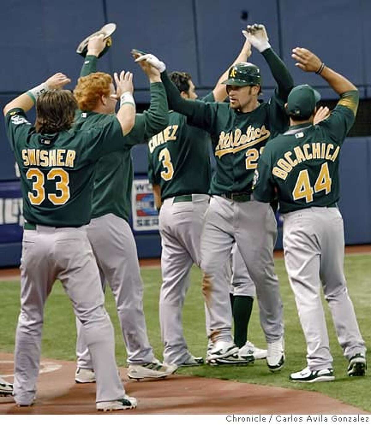 Mark Kotsay high fived by teammates after his two-run inside-the-park homerun in the top of the seventh inning to give the Athletics a 4-2 lead. The A's won 5-2 after Nick Swisher scored on a wild pitch by closer Joe Nathan. The Oakland Athletics played the Minnesota Twins in Game 2 of the American League Division Series at the Metrodome in Minneapolis, Mn., on Wednesday October 4, 2006, winning the game, 5-2. Photo by Carlos Avila Gonzalez/The San Francisco Chronicle Photo taken on 10/4/06, in Minneapolis, Mn, USA **All names cq (source)