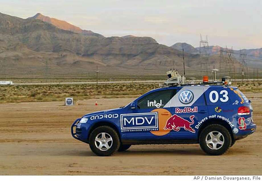 ** FILE ** Stanford Racing Team's unmanned Volkswagen, races through the Mojave Desert near Primm, Nev., in this Oct. 8, 2005, file photo, during the Defense Advanced Research Projects Agency (DARPA) 2005 Grand Challenge robot race sponsored by the Pentagon. Stanford University, whose unmanned Volkswagen dubbed Stanley won last year's desert race, was among 11 teams selected Monday, Oct. 2, 2006, to receive government money to participate in a contest requiring robots to carry out a simulated military supply mission. (AP Photo/Damian Dovarganes) OCT. 8, 2005 FILE PHOTO Photo: DAMIAN DOVARGANES