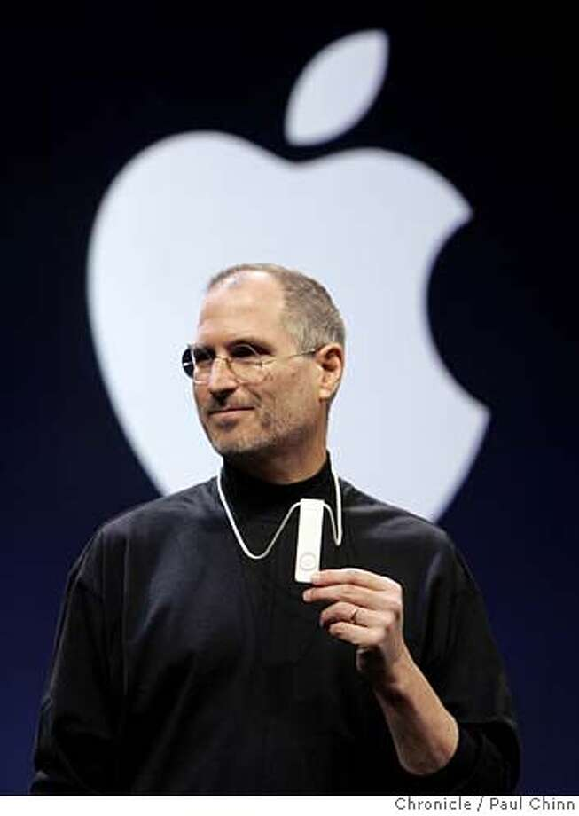 macworld12_191_pc.jpg  Steve Jobs shows off the tiny new iPod Shuffle. Apple CEO Steve Jobs unveiled the new Mac Mini desktop computer and the iPod Shuffle during his keynote speech at the 2005 Macworld show on 1/11/05 in San Francisco, CA.  PAUL CHINN/The Chronicle Ran on: 01-12-2005 Ran on: 01-12-2005 Ran on: 04-17-2005 MANDATORY CREDIT FOR PHOTOG AND S.F. CHRONICLE/ - MAGS OUT Photo: PAUL CHINN