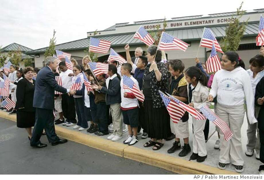 President Bush, left, and principle Silvia Ulmer, far left, greet students waving U.S. flags outside the entrance to the George W. Bush elementary school, Tuesday, Oct. 3, 2006 in Stockton, Calif. (AP Photo/Pablo Martinez Monsivais) Photo: PABLO MARTINEZ MONSIVAIS