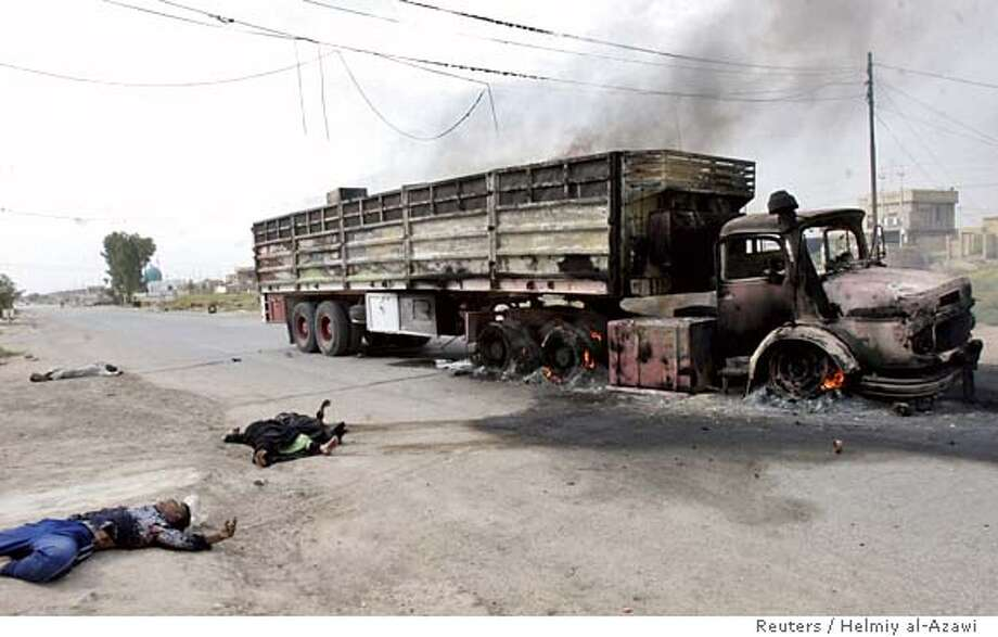 Bodies lie on the road close to a partially burnt truck near Baquba October 3, 2006. Four Shi'ite family members and their driver were travelling with their belongings to move to another place when killed by gunmen after being stopped on the road, police said REUTERS/Helmiy al-Azawi (IRAQ) 0 Photo: HELMIY AL AZAWI