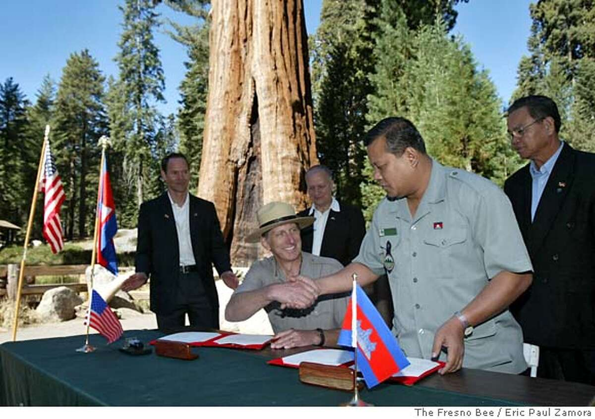 Craig Axtell, superintendent of Sequoia and Kings Canyon Nationals Parks, center seated, shakes hands with Mr. Chay Samith, right, director of the Department of Nature Conservation and Protection for the Kingdom of Cambodia's Ministry of Environment during the ceremony proclaiming sister hood betwen Sequoia and Kings Canyon National Parks and Cambodia's Samlaut Multiple Use Area. Photographed at Giant Forest in Sequoia National Park, CA on Tuesday, Oct. 3, 2006 in front of The Sentinel, a giant sequoia 257 feet high and 28 feet in diameter. ERIC PAUL ZAMORA-THE FRESNO BEE
