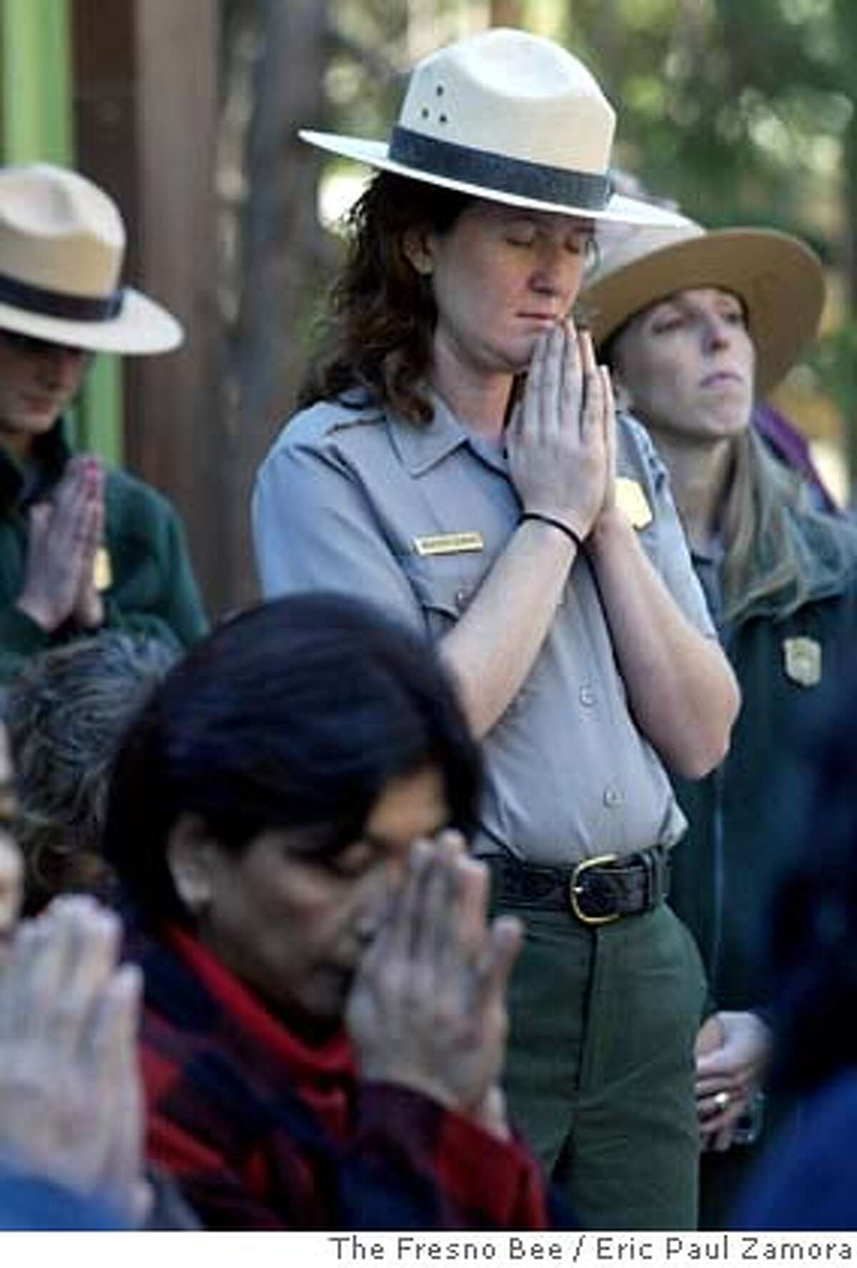 Heather Dumais, an air monitoring technician for Sequoia and Kings Canyon National Parks, bows her head during a prayer led by two Buddhist monks during the ceremony naming Sequoia and Kings Canyon National Parks sister parks to Cambodia's Samlaut Multiple Use Area on Tuesday, Oct. 3, 2006 in Giant Forest, Sequoia National Park. Photographed at Giant Forest in Sequoia National Park, CA on Tuesday, Oct. 3, 2006. ERIC PAUL ZAMORA-THE FRESNO BEE