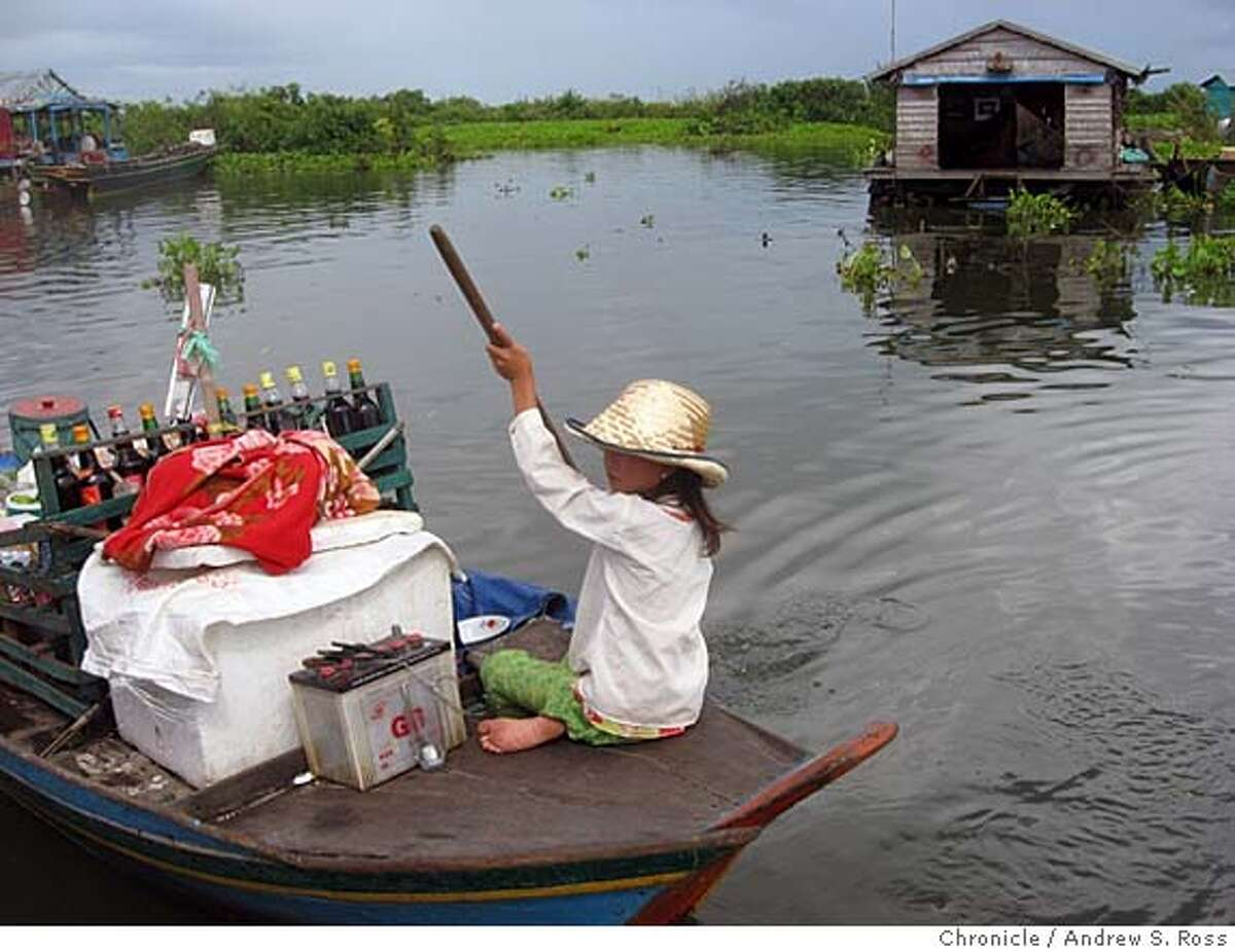 """Plying trade at Chong Neas, literally a """"floating village"""" in northern Cambodia whose residents, many of them Vietnamese refugees, make their living entirely on the water. Credit: Andrew S. Ross/The Chronicle"""