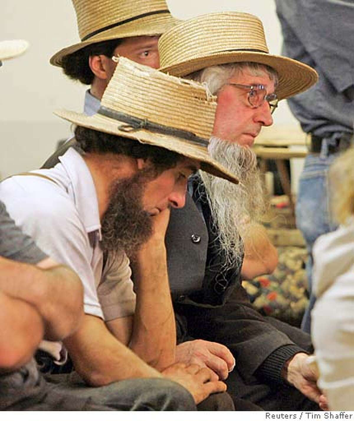 A group of Amish men react as Cmdr Jeffrey Miller (not shown) comments on the shooting at the Georgetown School in the town of Nickel Mines near Lancaster, Pennsylvania October 2, 2006. Gunman Charles Carl Roberts opened fire in the school killing three girls and wounding seven others before turning the weapon on himself, police said. REUTERS/Tim Shaffer (UNITED STATES)