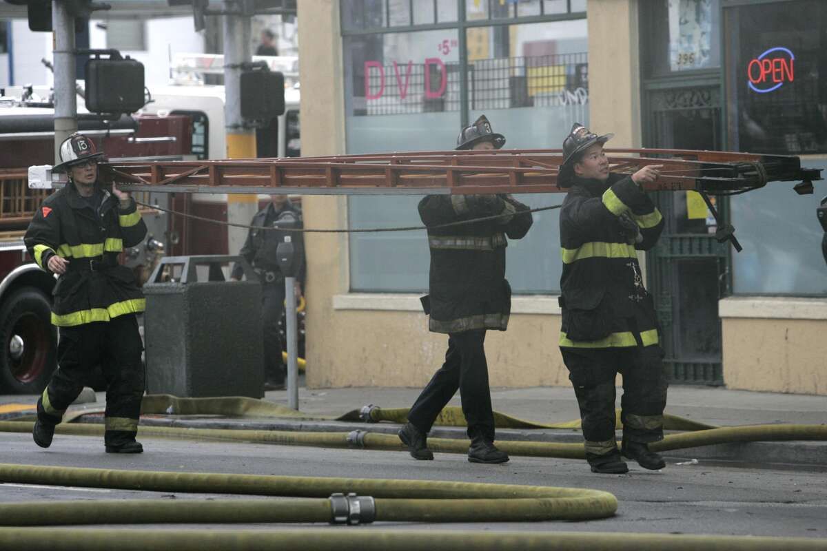 Firefighters rush toward the building carrying a ladder. The San Francisco Fire Department fights a four-alarm fire on Fifth Street between Harrison and Folsom on October 2, 2006.
