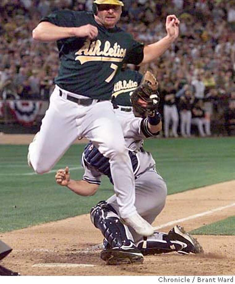ATHLETICS6-13OCT01-SP-BW--Jeremy Giambi leaps high into the air but is tagged out by Jorge Posada in the seventh inning trying to score from first. By Brant Ward/Chronicle Photo: BRANT WARD