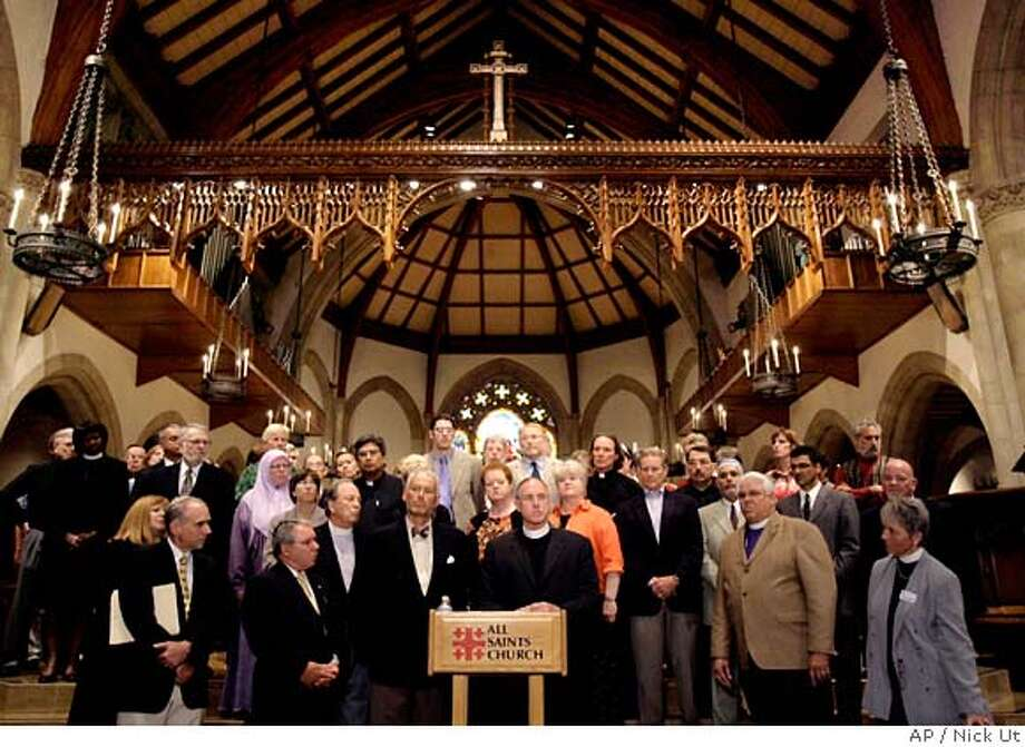 Rev. Edwin Bacon Jr., center, rector of the All Saints Church, speaks during a news conference while surrounded by supporters in Pasadena, Calif., Thursday, Sept. 21, 2006. The church's decision Thursday not to cooperate with an IRS investigation into an anti-war sermon delivered before the 2004 presidential election sets up a high-profile confrontation between the liberal congregation and the IRS, which usually keeps such inquiries private. The leaders of the 3,500-member All Saints Church voted unanimously to resist an order to turn over documents related to the sermon, which was given just two days before the election. The decision means the IRS must decide whether to ask the Justice Department to pursue the case in court. (AP Photo/Nick Ut) Photo: NICK UT