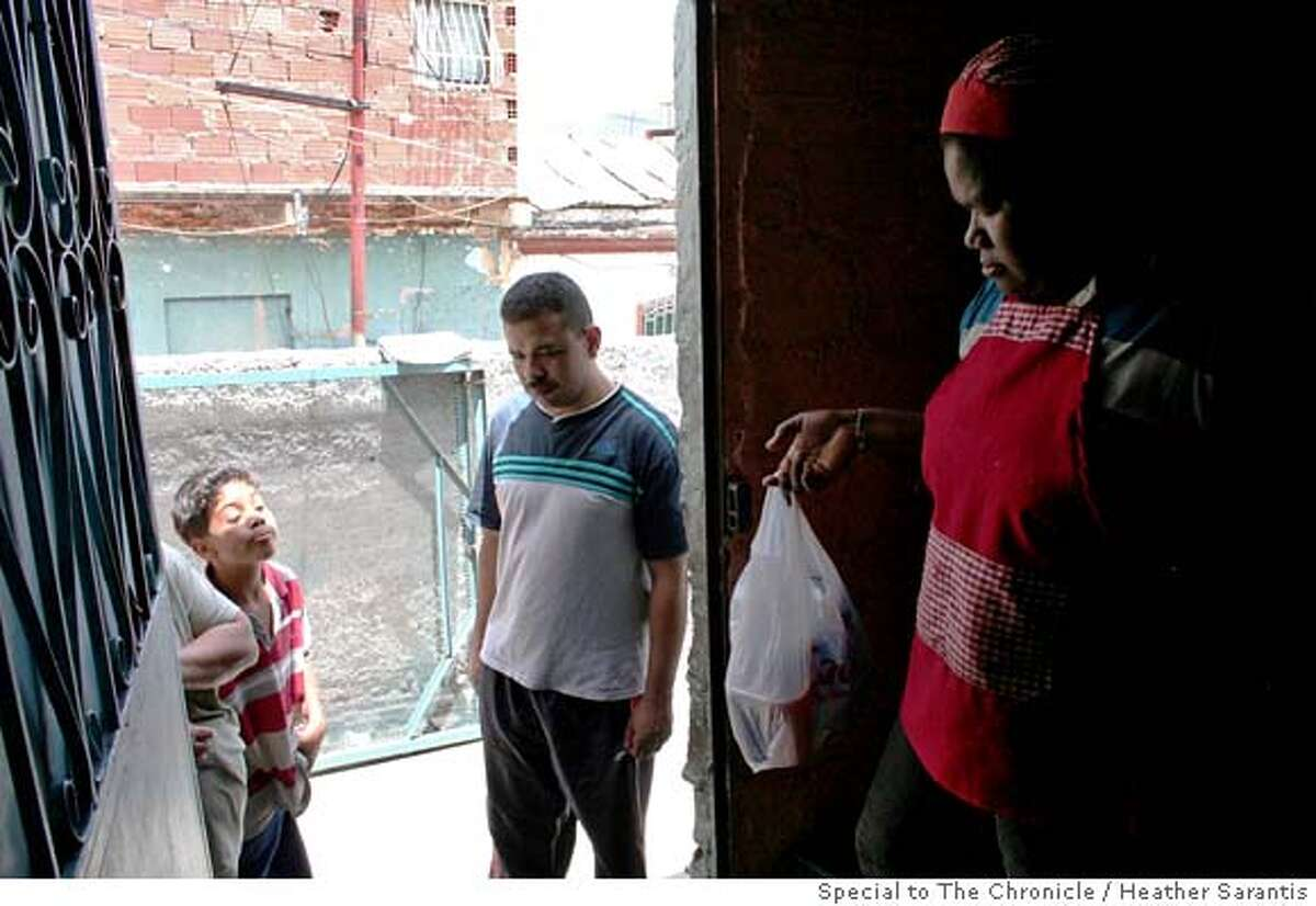 Raquel Cacera, a worker at a Casa de Alimentacion (Feeding House) in Caracas hands out lunches to local low income people. These government soup kitchens feed tens of thousands of people a day. Photo by Heather Sarantis/Special to The Chronicle