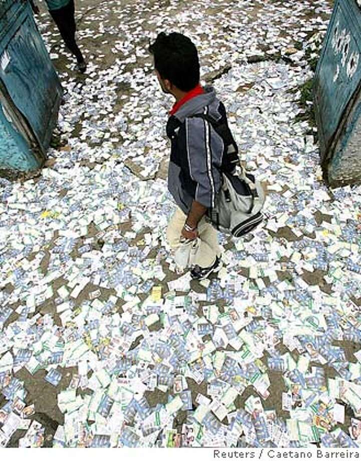 A man walks over propaganda leaflets covering a sidewalk, as Brazilians went to the polls to vote in general elections in Sao Paulo, October 1, 2006. REUTERS/Caetano Barreira (BRAZIL) 0 Photo: CAETANO BARREIRA