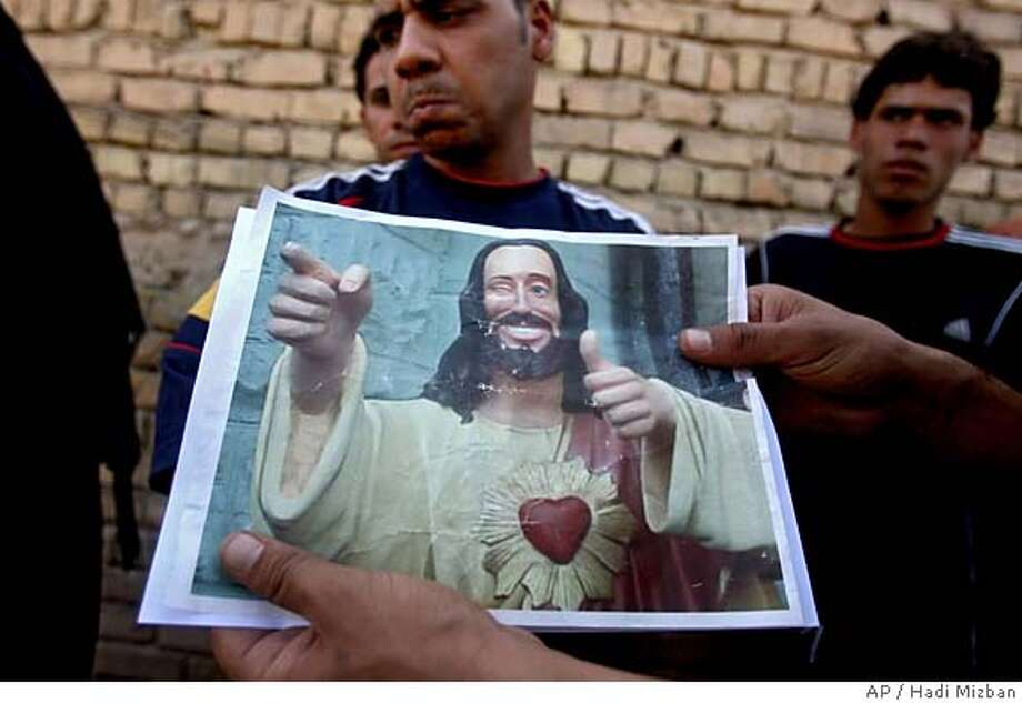 "** CAPTION CORRECTION, REMOVES SECOND SENTENCE ** A man displays an image of the character known as ""Buddy Christ"" which local residents claim was left by the US forces after an early-morning raid by Iraqi forces and their US advisers in Baghdad's Sadr City, Saturday, Oct. 1, 2006. (AP Photo/Hadi Mizban) Photo: HADI MIZBAN"
