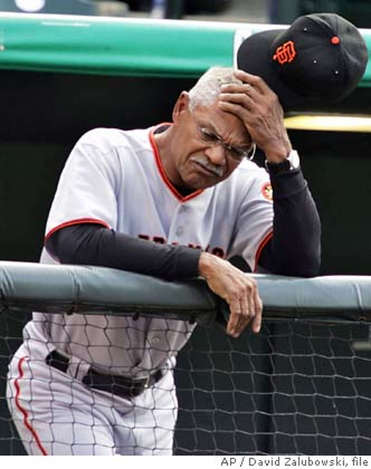 ** FILE ** San Francisco Giants manager Felipe Alou holds his head as he leans over the rail while looking on as pitcher Brad Hennessey falls behind in the count to Colorado Rockies' Todd Helton in a baseball game in Denver on May 18, 2005. Alou plans to fly home to Florida and then the Dominican Republic as soon as the season ends, even if his future with the Giants has yet to be resolved. (AP Photo/David Zalubowski, file)