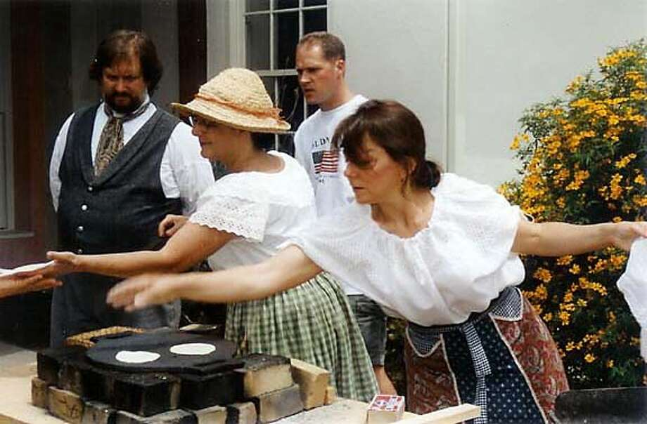State park volunteers Rosie Pettas (in hat) and Bev Paxton put tortillas on the comal (Mexican-style cast-iron grill) as part of the living history experience at the History Fest Monterey. Photo courtesy of History Fest Monterey