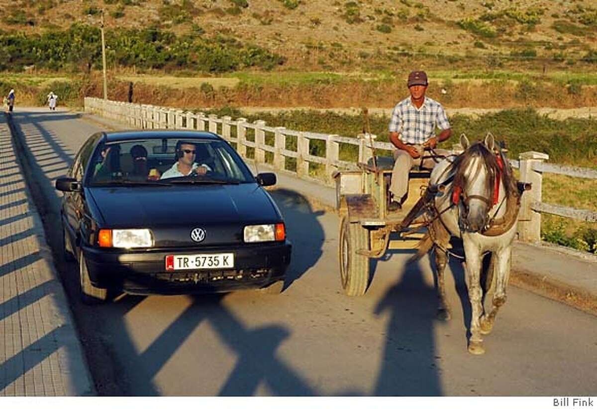 albania__081706001.JPG photo of horse drawn wagon and car side by side... --rush hour, near Mesi, northern Albania. Horse wagon had Mercedes hubcaps, just missed them in the photo Photographs to go with a Chronicle magazine story about vacationing in Albania. Bill Fink/Special to the Chronicle MANDATORY CREDIT FOR PHOTOG AND SAN FRANCISCO CHRONICLE/ -MAGS OUT