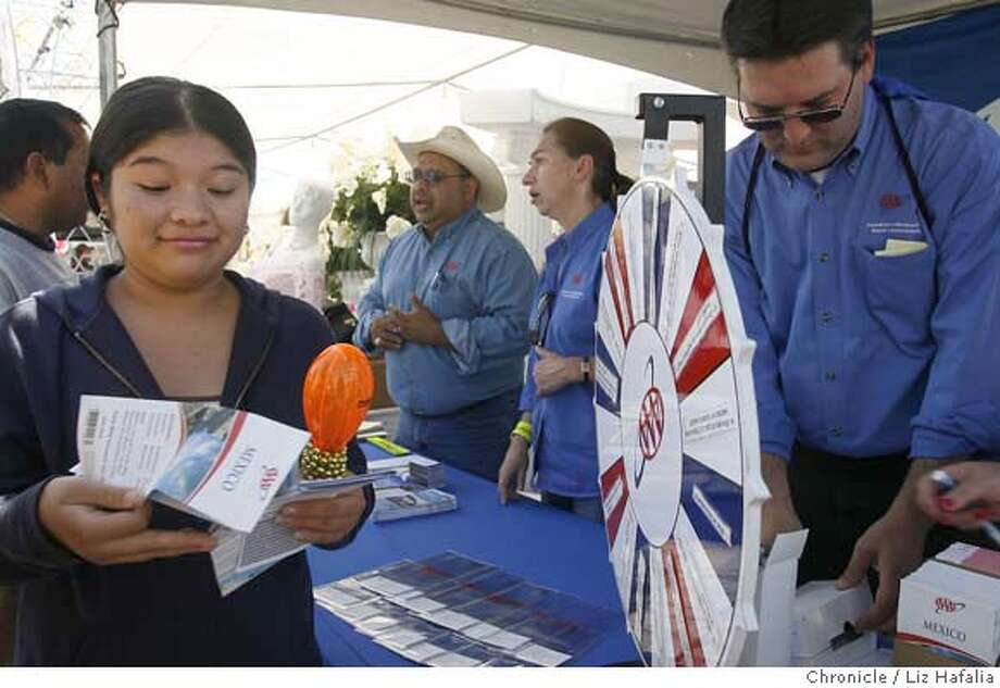 .JPG California AAA, which has started a Hispanic initiative to attract Latino car-club members, has their parade float and booth on Sunday, September 17th at the Redwood City North Fair Oaks Community Festival. Kenia Cabrera (left), 15 years old, got free maps of Mexico and Baja. Sales representative Clinton S. Ward at right.  . Liz Hafalia/The Chronicle MANDATORY CREDIT FOR PHOTOGRAPHER AND SAN FRANCISCO CHRONICLE/ -MAGS OUT Photo: Liz Hafalia