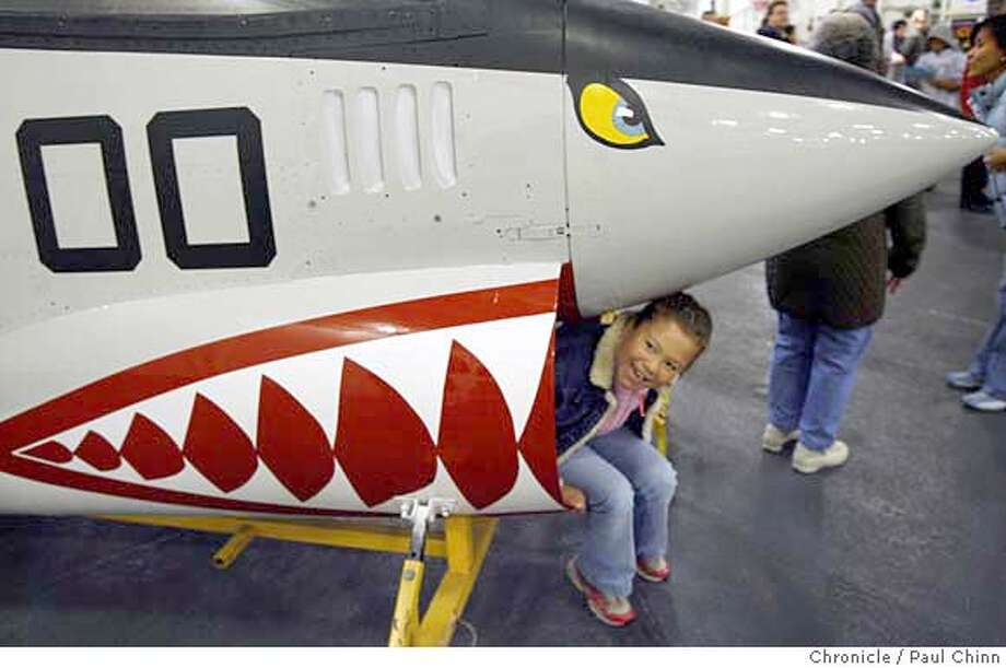 Eight-year-old Rebecca Fraser of Milpitas tries to squeeze into the air intake of an F8 Crusader fighter jet at the Troopfest concert and festival aboard the USS Hornet aircraft carrier museum in Alameda, Calif. on Saturday, Sept. 30, 2006. Proceeds from the fundraiser will go towards holiday gift packages for U.S. troops serving in Afghanistan and Iraq.  PAUL CHINN/The Chronicle  **Rebecca Fraser MANDATORY CREDIT FOR PHOTOGRAPHER AND S.F. CHRONICLE/ - MAGS OUT Photo: PAUL CHINN